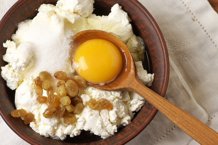 Cooking ingredients for cheesecakes: cottage cheese, sugar, raisin and yolk. photo