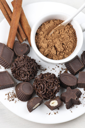 Homemade natural chocolate candies with ingredients on white plate. photo
