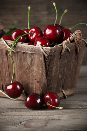 Cherries in basket on vintage wooden  photo