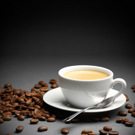 Coffee cup and beans on dark gray  photo