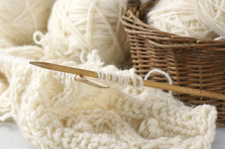 Natural woolen yarn and knitting close-up. Imagens
