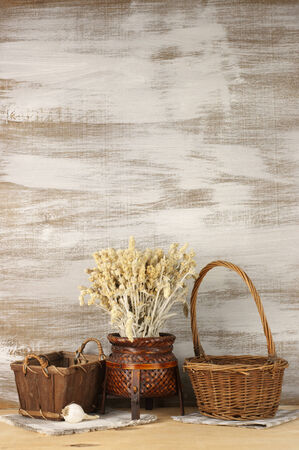 Wicker baskets with dry flowers on rustic wooden background. photo