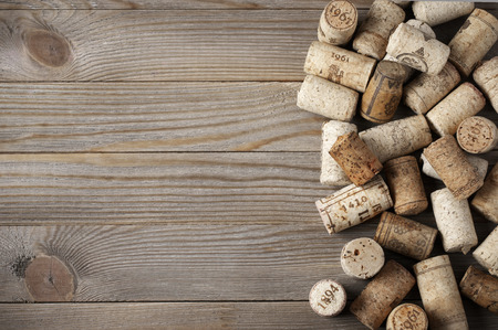 Heap of assorted wine corks on wooden background.