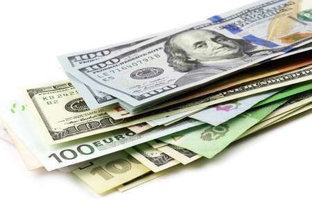 Pile of various currencies on white background.