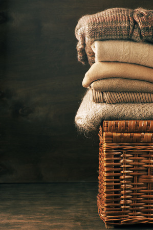 Stack of knitted sweaters on wicker basket. photo