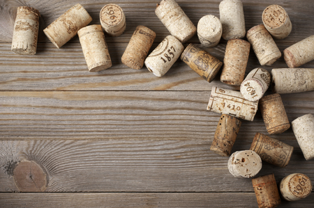 Heap of assorted wine corks on wooden background. photo
