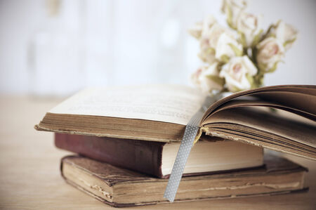 Stack of books and roses on wooden table. Shallow DOF. photo