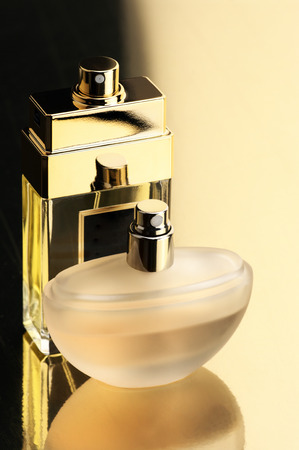 Two perfume bottles on gold background with reflection. photo