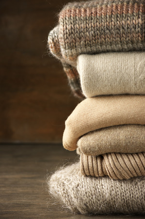 Stack of knitted sweaters on wooden background. photo