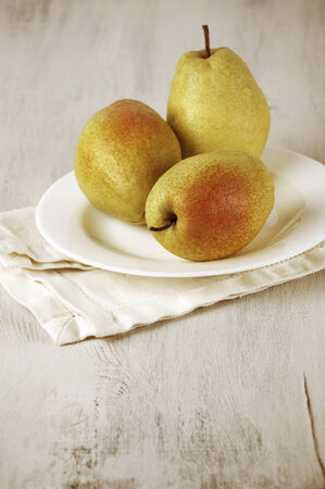 Three ripe pears in plate on white wood. photo