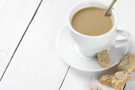 Cup of coffee with milk and almond cookies on white wooden table. photo