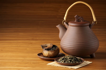 Assorted tea and ceramic teapot on wooden background with copy space. photo