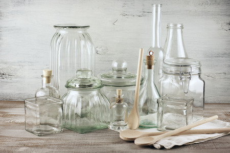 Collection of various glassware and wooden spoons on vintage wood. photo