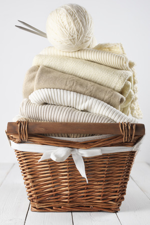 Stack of warm sweaters in basket on white wood. photo