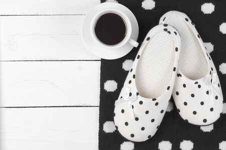 Pair of feminine slippers with white and black polka dot decor, woolen knitwear and cup of coffee on white wood. photo