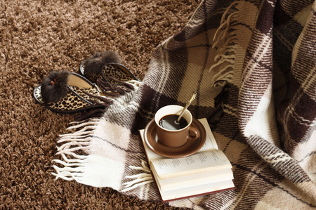 Woolen plaid, coffee cup, book and slippers on shaggy carpet. Top view. photo