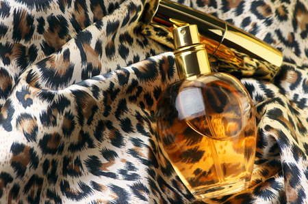 Bottle of woman perfume and gold lipstick on animal style headscarf. photo
