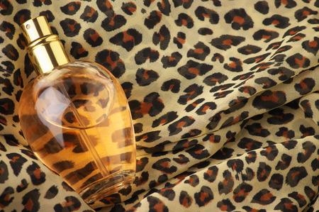 Bottle of woman perfume on animal style headscarf. photo