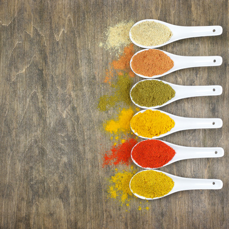 chili powder: Assorted powder spices in white spoons on wood. Top view point.