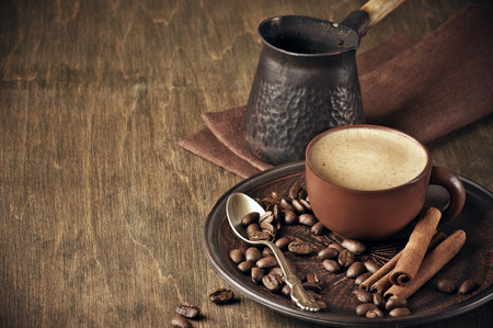 Coffee cup, beans, cinnamon and cezve on vintage wooden background. photo