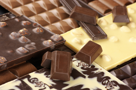 Pile of assorted chocolate bars close-up.