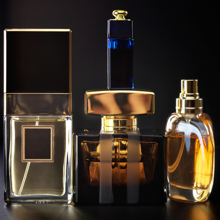 Various bottles of woman perfume on dark background. photo