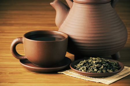 tazza di th�: Close-up di t� essiccate, tazza di t� e teiera su sfondo di legno.