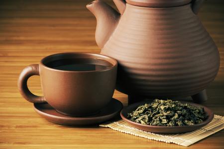 taza de t�: Primer plano de t� seco, una taza de t� y la tetera en el fondo de madera.