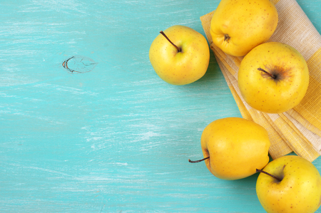 Yellow Golden Delicious apples with linen napkin on turquoise rustic wooden table. Top view point. photo