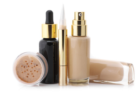 Two glass bottle of liquid foundation, corrective concealer, loose mineral powder and face serum isolated on white background. photo