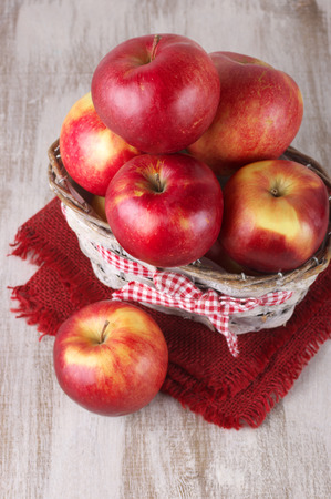 Red apples in basket with napkin on rustic painted wooden table. photo