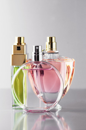 Three various bottles of woman perfume on gray background. Imagens