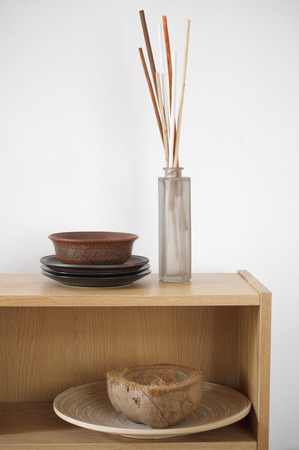 Wooden shelf with decorative elements against white wall. photo
