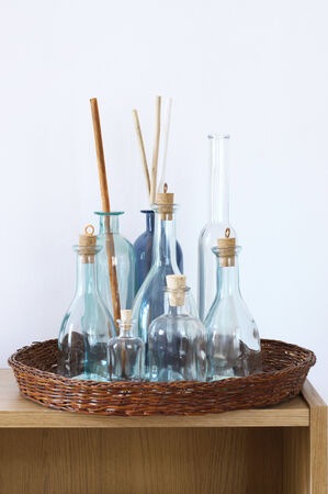 Wooden shelf with decorative bottles against wall. photo