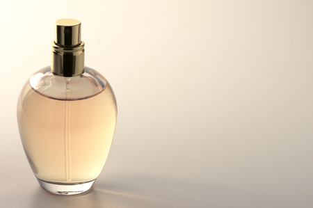 Bottle of woman perfume on light background with copy space. Toned image.
