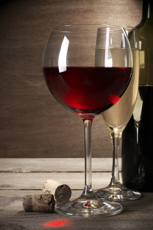 still life of wine: Glasses of red and white wine and bottle with corks on rustic wooden background. Stock Photo