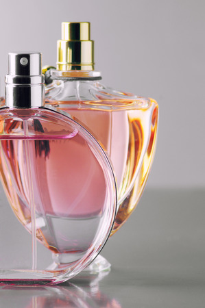 Two various bottles of woman perfume on gray background. photo