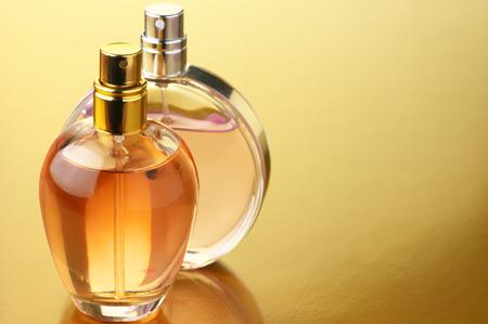 コピー スペースとゴールドの背景に女性の香水の 2 つのボトル。 写真素材