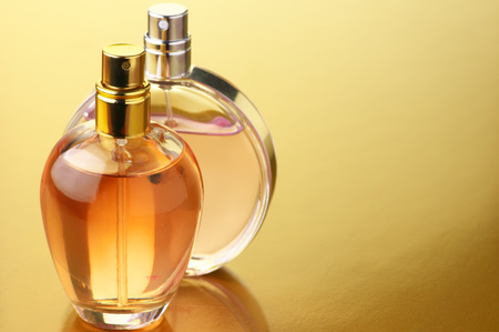 Two bottles of woman perfume on gold background with copy space. Stockfoto