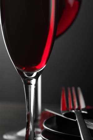 Close-up of two glass of red wine, plates and silverware on dark wooden table. Shallow DOF. photo