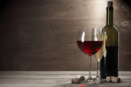 Glasses of red and white wine and bottle with corks on rustic wooden background with copy space. photo