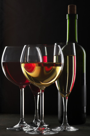 Various glasses of red and white wine with abstract pattern and bottle on black wooden background. photo
