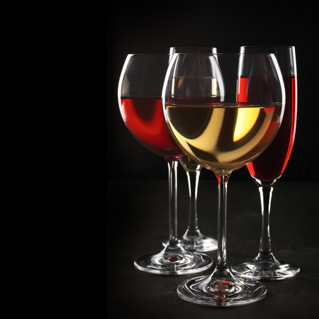 Various glasses of red and white wine with abstract pattern on black background. photo