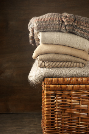 mohair: Stack of knitted sweaters on wicker basket.