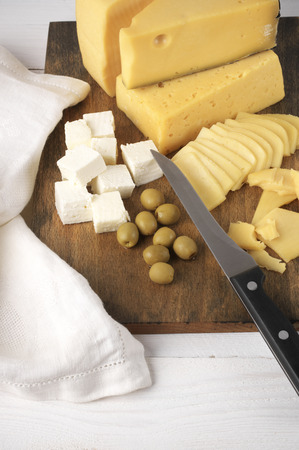 Assorted cheese with olives on vintage board on rustic wooden background. photo