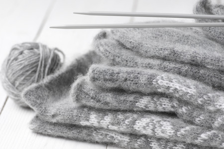 Stack of gray warm fluffy knitwear with knit needles and ball on white wood. photo