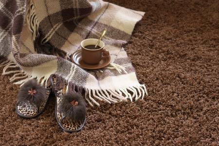 Woolen checked plaid, slippers and coffee cup on shaggy carpet. Focus on slippers. photo