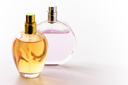 Two bottles of woman perfume on light background with copy space.