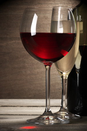 Glasses of red and white wine and bottle on rustic wooden background. photo