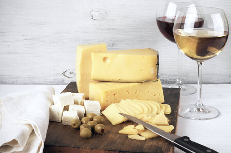 Assorted cheese with olives on board and glasses of red and white wine on rustic wooden background. photo